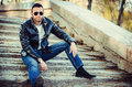 Guy with attitude wearing leather jacket and sunglasses out sexy outdoors Royalty Free Stock Photo