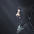 A guy in a black robe standing in the dark under rays of moon Royalty Free Stock Images