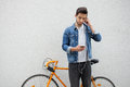 The guy in a blue denim jacket standing on wall background.  young man near orange bicycle. Smiling student with bag Royalty Free Stock Photo