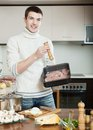 Guy cooking meat with mushrooms and potatoes adding raw in roasting pan Royalty Free Stock Photography