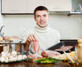 Guy cooking raw meat ordinary at kitchen Stock Photo