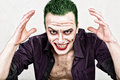 Guy with crazy joker face, green hair and idiotic smike. carnaval costume