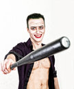 Guy with crazy joker face holding baseball bat, green hair and idiotic smike. carnaval costume