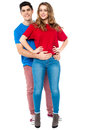 Guy embracing his girl from behind arms around handsome young men girlfriend her waist Royalty Free Stock Photo