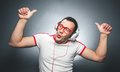 Guy enjoying in music funny man dancing and listening with headphones over dark gray background studio shot Stock Images