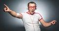 Guy enjoying in music funny man dancing and listening with headphones over dark gray background studio shot Stock Photos