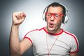 Guy enjoying in music young trendy man dancing and listening with headphones over dark gray background studio shot Stock Image