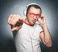 Guy enjoying in music young trendy man dancing and listening with headphones over dark gray background studio shot Royalty Free Stock Photos