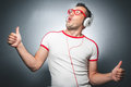 Guy enjoying in music young trendy man dancing and listening with headphones over dark gray background studio shot Royalty Free Stock Photo