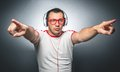 Guy enjoying in music young trendy man with raised arms dancing and listening with headphones over dark gray background studio Royalty Free Stock Image
