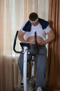 Guy exercising on stationary training bicycle and looking at his fat stomach