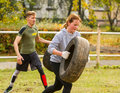 Guy and girl exercising with a tire.