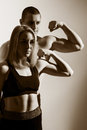 Guy and girl flex biceps. Royalty Free Stock Photo
