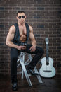 The guy with the guitar big muscles sits next to Royalty Free Stock Photos