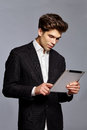 Guy with hairstyle holding tablet and working on it Royalty Free Stock Photo