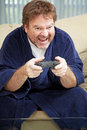 Guy at home playing video games unemployed man in his bathrobe plays all day Stock Photos