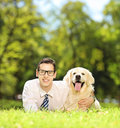 Guy lying on a green grass and hugging his dog in a park labrador retriever shot with tilt shift lens Royalty Free Stock Photos
