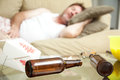 Guy passed out at home man on his couch in his underwear a full ashtray empty beer bottles and empty chinese take container Stock Image