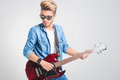 Guy playing guitar in studio while wearing sunglasses Royalty Free Stock Photo