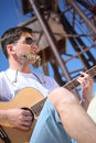Guy plays guitar and  lip accordion sitting Royalty Free Stock Photos