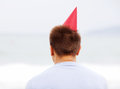 Guy in red hat near sea from behind lonely young man party sitting ocean Stock Photo