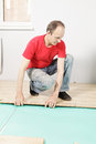 Guy in red installing flooring Stock Photo