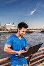 A guy sitting with laptop out outdoor next to the sea side Stock Photos