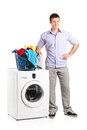 Guy standing by a washing machine full length portrait of with laundry basket on it isolated on white background Stock Images
