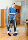 Guy sweeping the floor at home smiling in living room Stock Photo