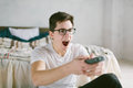 Guy using remote control while sitting on the bed in home. Happy attractive young man watching tv . Human emotions on Royalty Free Stock Photo