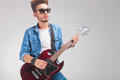 Guy wearing sunglasses while playing the guitar Royalty Free Stock Photo