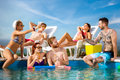 Guys and girls refreshes on swimming pool with drinks Royalty Free Stock Photo