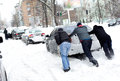 The guys are pushing a car stuck in the snow Royalty Free Stock Photo