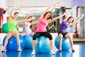 Gym fitness women training and workout young doing sports or with gymnastic ball in a Royalty Free Stock Photo