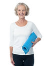 Gym instructor holding blue exercise mat cheerful female fitness Stock Images