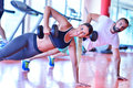 Gym man and woman push-up strength pushup with dumbbell in a workout Royalty Free Stock Photo