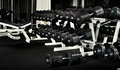 Gym many black dumbbells in dark weight room horizontal photo Stock Image