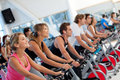 Gym people on spinning machines Royalty Free Stock Images