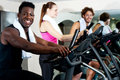 Gym trainer exercising along with his trainees group of smiling people at the doing cardio exercise Stock Image