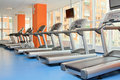 Gym with windows and running machines in fitness center Royalty Free Stock Image