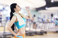 Gym woman drinking water from a bottle shot at fitness center Stock Image