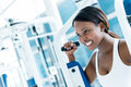 Gym woman exercising on a machine and looking happy Stock Photo