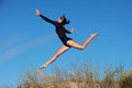 Gymnast jumping joyfully on the beach a is doing her routine in south africa Stock Photo