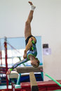 Gymnastics girl courage beam somersault young with on the doing a flip her routine program at the regional competition held at Stock Image