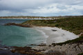Gypsy cove curved sandy beach of in the falkland islands the is home to a breeding colony of magellanic penguins spheniscus Stock Image