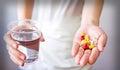 Hände mit pillen und glas wasser lokalisiert auf weiß Stockbilder