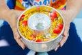 Händer av kvinnahållbunken av vatten som är blandad med doft och den livliga blommablomkronan songkran festival av thailand Royaltyfria Foton