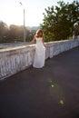 Härlig flicka i en vitklänning i strålarna och ilsken blick av sunen Royaltyfri Foto