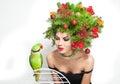 Härlig idérik xmas makeup och hårstil sköt inomhus skönhetmodemodell girl med den gröna papegojan Arkivfoto