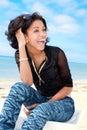 Härlig karibisk brunett som sitter på stranden Fotografering för Bildbyråer